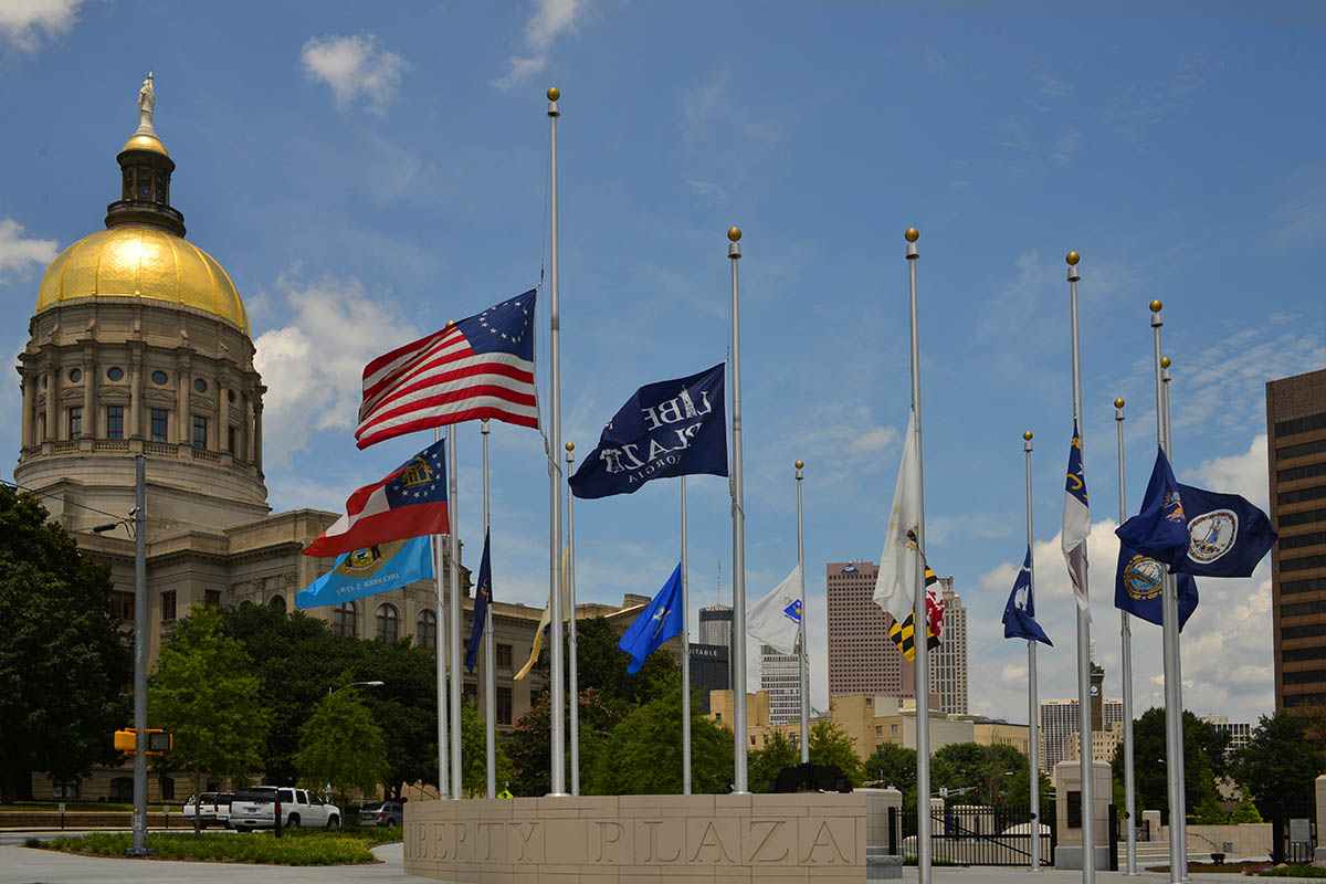 Flags at Liberty Plaza fly at half-staff yesterday